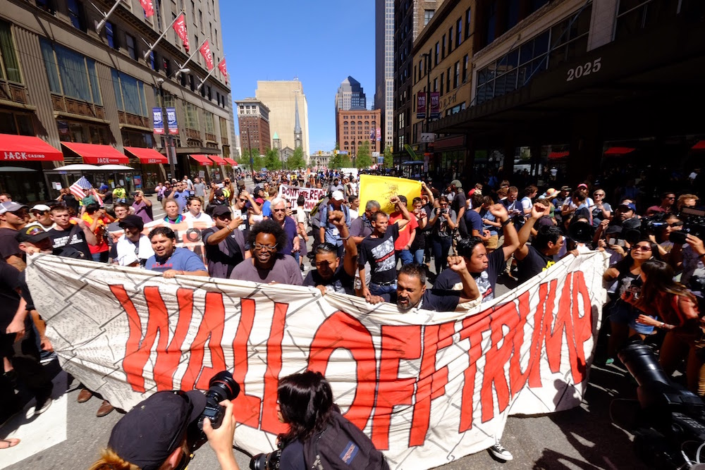 Activists marching with Wall Off Trump Banner
