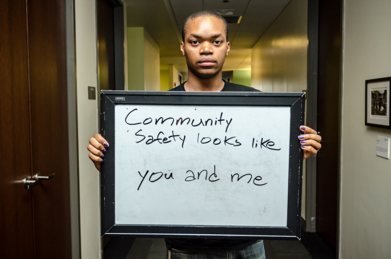 "Man holding sign that says, ""Community safety looks like you and me"""